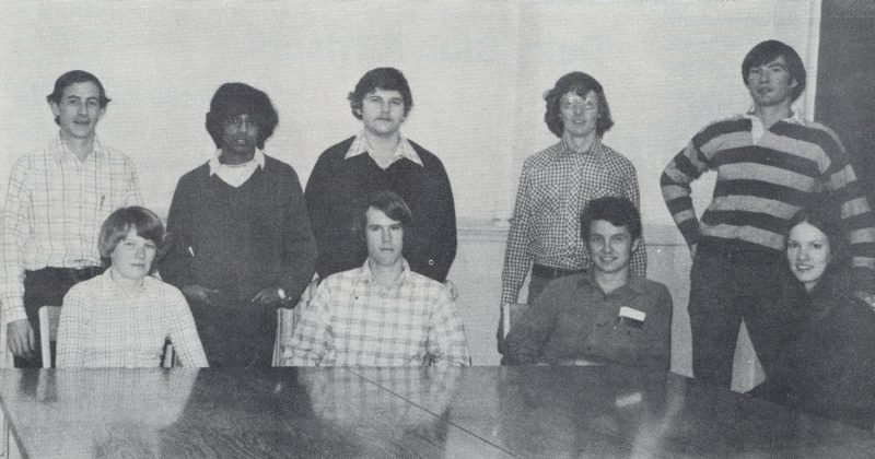 "From the 1976 Milky Way.  Graduate Students. ""They keep the research going!"" (L to R) Seated: Margaret Jamison, John Clay, Ted Friend, Mary Sowerby. Standing: John Chandler, Mahendra DeSilva, Mike Akers, Mike O'Conner, Chuck Sera."
