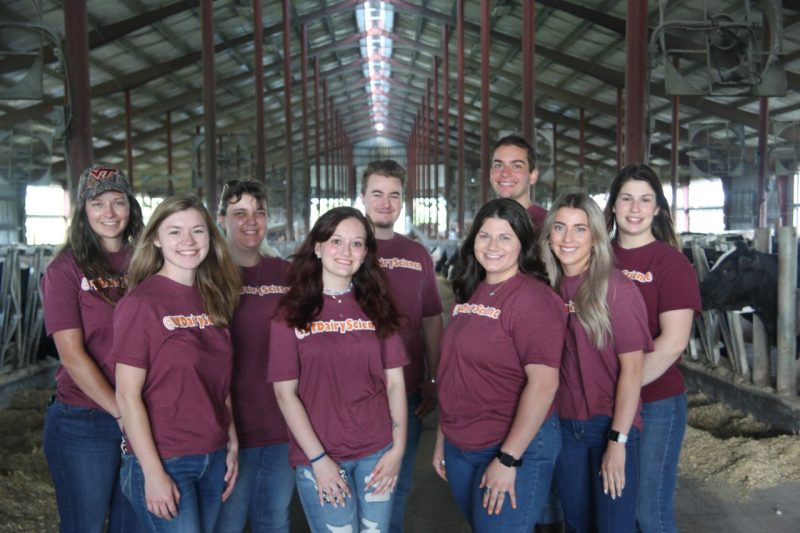 The ten  2018-219 student dairy ambassadors in maroon @vtdairyscience shirts and blue jeans posing in front of a hokie stone facade.
