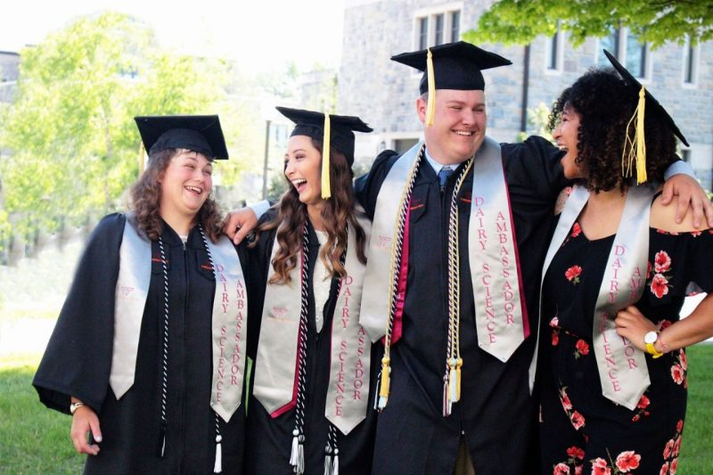 Spring 2018 graduating ambassadors in graduation regalia, laughing together.